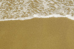 Gentle bubbles wave on the fine yellow sand background Royalty Free Stock Photo