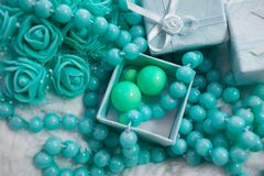 Delicate composition of costume jewelry color of mint and turquoise. Gentle color composition of mint and turquoise jewelry. Beads and roses from the box as a Stock Image