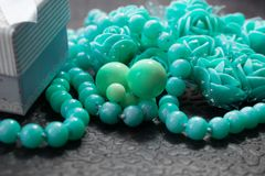 Delicate composition of costume jewelry color of mint and turquoise. Gentle color composition of mint and turquoise jewelry. Beads and roses from the box as a Royalty Free Stock Photos