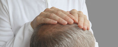 The Gentle Comfort of Hands on Healing. Close up of the back of a man's head with a pair of female hands placed on his crown channeling healing energy Stock Images