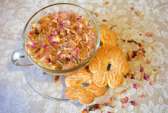 Gentle composition of the drink of tea rose petals, transparent cup and saucer, cookies in the shape of flowers and scattered peta Royalty Free Stock Photo