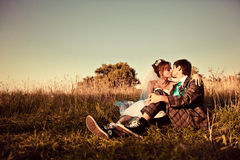 Gentle couple is  sitting and kissing  on the background tree an Royalty Free Stock Photography