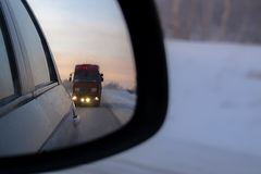 The gentle dawn of a frosty morning in the rear view mirror. stock images