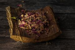 Gentle dried rose petals on a tree bark. On a wooden background. With bud of klyteria stock photo