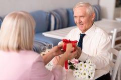 Gentle elderly man presenting a surprise box Royalty Free Stock Photo