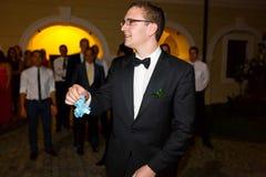Gentle elegant groom is holding garter on the background restaur Stock Photo