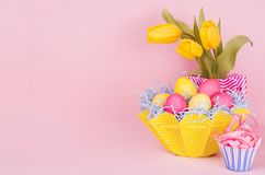 Gentle elegant soft pastel easter decoration - painted eggs, yellow tulips, cupcake on pink background, copy space. Gentle elegant soft pastel easter decoration Royalty Free Stock Image