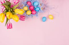 Gentle elegant soft pastel easter decoration - painted eggs, yellow tulips, cupcake on pink background, copy space, top view. Stock Images