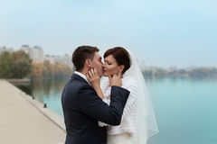 Gentle embrace bride and groom. Groom kissgroom kiss on the pier Stock Image