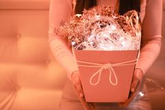 A girl with coral gift box and lights. New Year 2019 royalty free stock photo