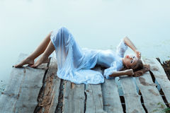 Gentle girl in white dress lying on a wooden pier. Royalty Free Stock Images