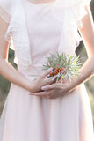 Gentle graceful hands of bride Girl with branch of sea buckthorn in the hand in a gentle air wedding dress in the sun rays at Royalty Free Stock Images