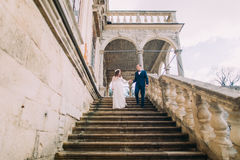 Gentle groom holding hand of his pretty bride when descending by antique palace stone stairs. Low angle shot Royalty Free Stock Images