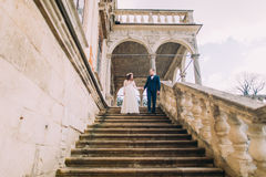 Gentle groom holding hands when going down with his pretty bride by antique palace stone stairs. Low angle shot Royalty Free Stock Photography