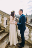 Gentle groom holding hands with his pretty bride while both stand on antique stone stairs Royalty Free Stock Photos