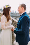 Gentle groom holding hands with his pretty bride while both stand on antique stone stairs. Close up Royalty Free Stock Photos