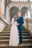 Gentle groom holding hands with his pretty bride while both stand on antique stone stairs. Full length portrait.  Royalty Free Stock Image