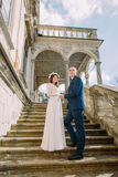 Gentle groom holding hands with his pretty bride while both stand on antique stone stairs. Low angle shot Stock Images