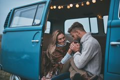 So gentle!. Handsome young men warming up his girlfriends hands while enjoying their road travel Royalty Free Stock Photos