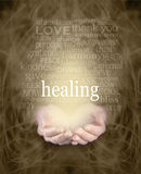 Gentle Healing Words. Female cupped hands with the word 'healing' floating above surrounded by a healing word cloud on a swirling misty sepia colored energy stock photo