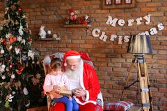 Young person girl shows Santa Claus interesting pictures in lar Stock Photography