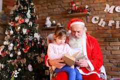 Young person girl shows Santa Claus interesting pictures in lar Royalty Free Stock Images