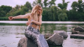 Gentle kind mermaid with blond hair and long tail sits on a stone in the lake and conjures over the water and smiles at. Her reflection, summer video shooting stock video