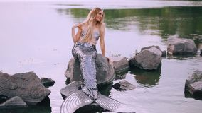 Gentle kind mermaid is sitting on a stone in the lake and smiling to the water, touching the shoulder with her hand. While the wind gently straightens her hair stock video