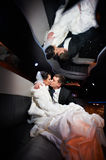 Gentle kiss bride and groom in wedding limo Stock Images