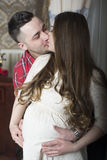 A gentle kiss-happy couple awaiting the birth of their child. Royalty Free Stock Images