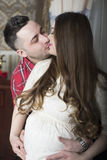 A gentle kiss-happy couple awaiting the birth of their child. Royalty Free Stock Photography