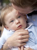 Gentle Kiss. A young baby boy is being gently kissed by his father. His father is holding and, while he is obviously has strength, his hold is gentle and tender Royalty Free Stock Images