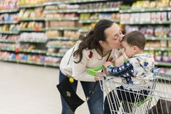 Gentle kisses mom with sons. Loving hugs. Mom gently kisses his young son in the supermarket.  royalty free stock photography
