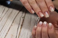 Gentle light manicure. On beautiful female hands Royalty Free Stock Images