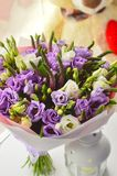 Gentle lilac bouquet with eustomy. In stylish packing on a white table at a window with a teddy bear on a floor stock photos