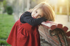 Gentle little girl near a bench in the park. Stock Image