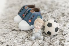 Gentle little newborn baby, a soccer ball and children`s sneaker stock photos