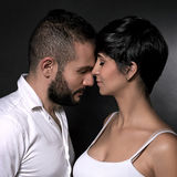 Gentle loving couple. Closeup portrait of gentle loving couple over black background, enjoying each other, romantic relationship, affection and tenderness Royalty Free Stock Photos