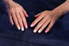 Gentle manicure on dark fabric. Royalty Free Stock Photo