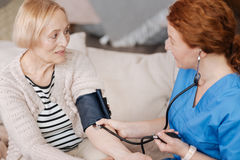 Gentle mindful nurse employing blood pressure sensor. Examination of pressure. Hardworking precise medical worker using professional equipment for testing and Royalty Free Stock Images