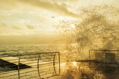 A gentle morning at the seaside. Black Sea. Wooden pier, water from the wave on the pier. Splash of a big wave, splashes against the background of the sun Royalty Free Stock Photos