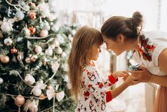 Gentle mother with her little daughter dressed in pajama next to the New Year`s tree in the full of light cozy room royalty free stock photos