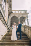Gentle newlywed groom holding hands with his pretty bride while both stand on antique stone stairs. Low angle shot Royalty Free Stock Image
