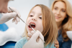 Gentle pediatric dentist doing a checkup Stock Photography