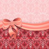 Gentle pink background with Victorian pattern divided satin ribbon with a bow. Stock Images