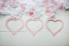 Gentle pink heart made of paper with white and pink flowers on white wooden table Stock Photos