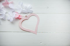 Gentle pink heart made of paper with white and pink flowers on white wooden table Royalty Free Stock Photos