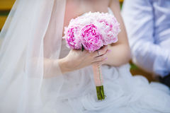 Gentle Pink Peony Bouquet in Hand of Sitting Bride. Gentle pink peony bouquet with handle in hands of bride sitting in white dress with bridal veil. Romantic Royalty Free Stock Image
