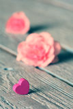 Gentle pink rose and heart on wooden table Royalty Free Stock Photography