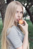 Gentle portrait of a beautiful cute girl with long blond hair with full lips and blue eyes with apple in hand, look at the camera Stock Photos